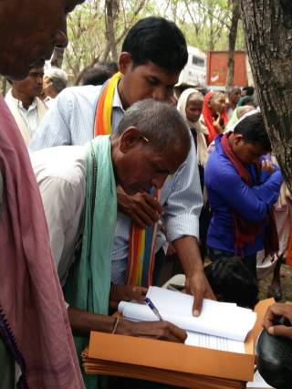3An Adivasi affected man signing his complaint before submitting to the police against illegal purchase of his land by private companies